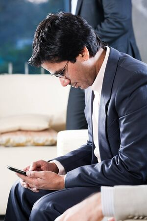 indian businessman sending or reading sms on his mobile phone with his colleague in the background photo