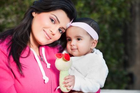 petite fille musulmane: Famille indienne, mère tenant sa petite fille dans les bras de Banque d'images