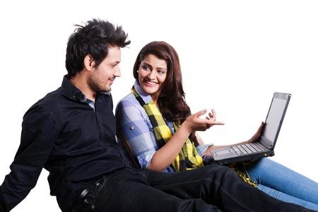 fille indienne: heureux jeune couple utilisant un ordinateur portable isol� sur blanc, couple multi ethnique isol� sur blanc