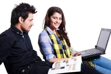 young couple selecting the flooring for the new home,happy young couple using laptop isolated on white, multi ethnic couple isolated on white  photo