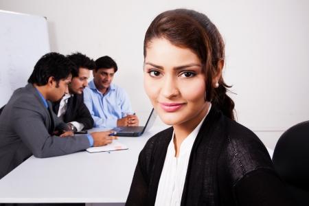 American Indian: retrato de una mujer de negocios feliz con sus colegas en el fondo