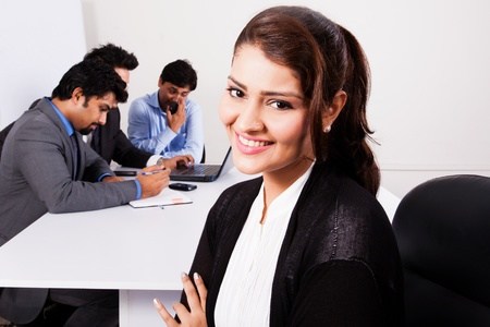 portrait of a happy businesswoman with her colleagues in the background photo