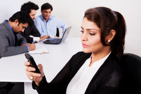 Indian businesswoman reading sms on mobile phone with he colleagues in the background photo