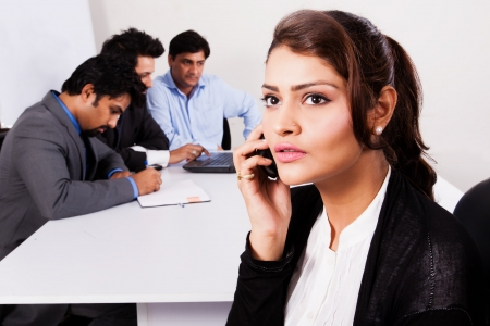 south asian: Indian businesswoman talking on the phone with her colleagues in the background