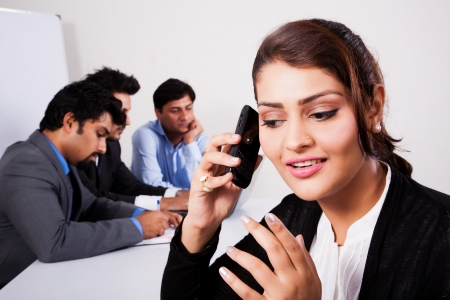 Indian businesswoman talking on the phone with her colleagues in the background photo