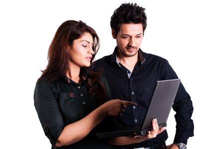 estudiantes universitarios: joven pareja multirracial usando la computadora port�til aislados en blanco