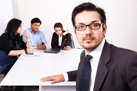 latin american: close up of a confident businessman with his colleagues in the background