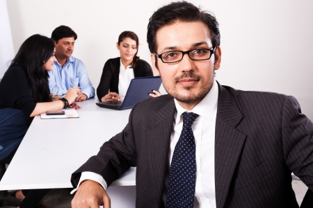 close up of a confident businessman with his colleagues in the background Stock Photo - 14548733