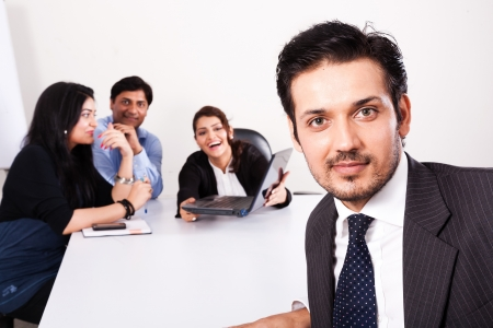 south american: close up of a confident businessman with his colleagues in the background