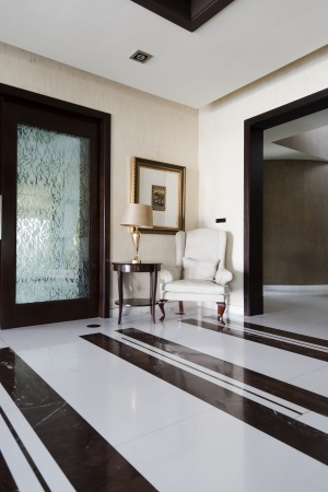 marble flooring: corner of a modern apartment with a classic chair and a paitning Stock Photo