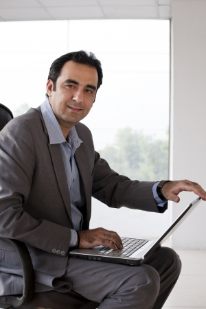 Portrait of a mature businessman using laptop photo