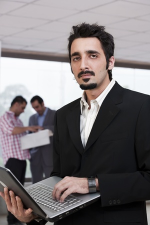 young businessman with colleagues in background photo