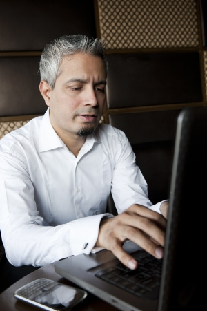 grey hair: portrait of a handsome businessman with grey hair working on the laptop, Indian muslim businessman working