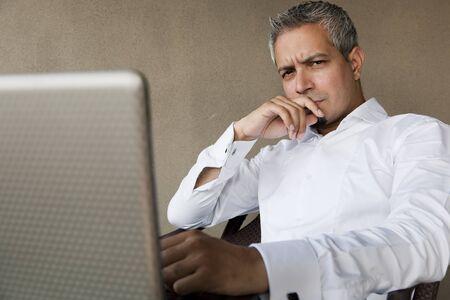 rich man: retrato de un apuesto hombre de negocios con el pelo gris que trabaja en la computadora port�til, hombre de negocios indio musulm�n de trabajo