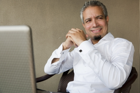 portrait of a happy successful businessman with grey hair working on the laptop, Indian muslim businessman working  photo