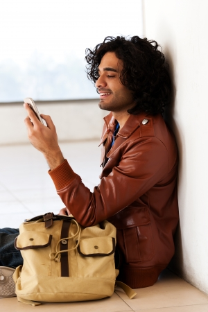 male university student sitting alone corridor,man sending or reading sms photo