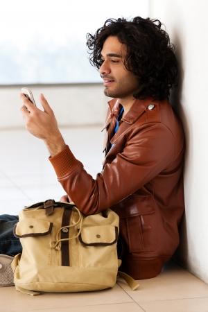 male university student sitting alone corridor,man sending or reading sms photo