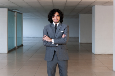 mixed race businessman standing in the office hall, portrait of a busineeman with copy space  photo