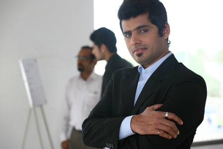 close up of a confident businessman with his colleagues in the background Stock Photo - 14863340
