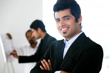 close up of a confident businessman with his colleagues in the background  photo