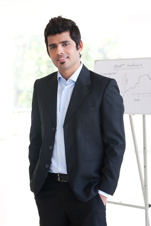 portrait of a confident Indian businessman standing in the boardroom with white board in the background photo