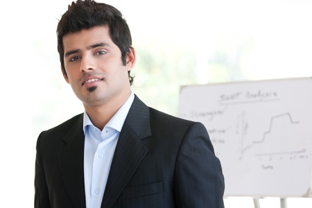 indian male: portrait of a confident Indian businessman standing in the boardroom with white board in the background