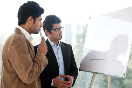 american banker: two businessmen discussing business strategy in a meeting, Indian business man with latin american colleague