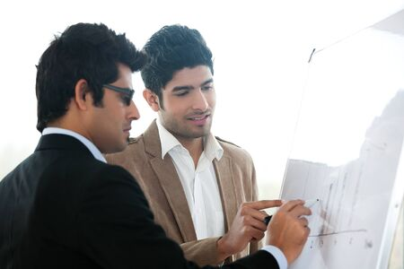 two businessmen discussing business strategy in a meeting, Indian business man with latin american colleague photo