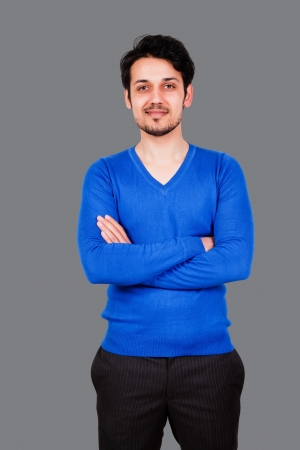 portrait of a handsome arab man wearing blue sweater, biracial man isolated on grey photo