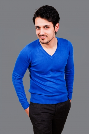 warm shirt: portrait of a handsome arab man wearing blue sweater, biracial man isolated on grey Stock Photo