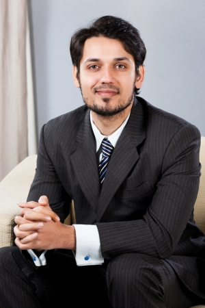 arab man: confident Indian businessman sitting on sofa Stock Photo