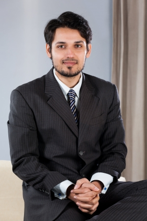 indian professional: confident Indian businessman sitting on sofa Stock Photo