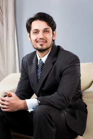 confident Indian businessman sitting on sofa Stock Photo