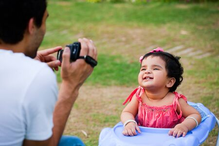 man taking pictures of his daughter photo