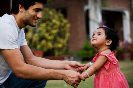 father helping his daughter to take first step of life Stock Photo