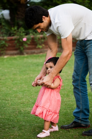 first step: Vater hilft seiner Tochter zum ersten Schritt des Lebens zu nehmen