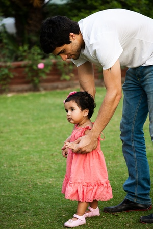 father helping his daughter to take first step of life photo