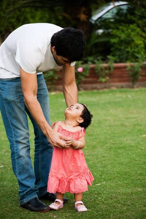 family support: father helping his daughter to take first step of life Stock Photo