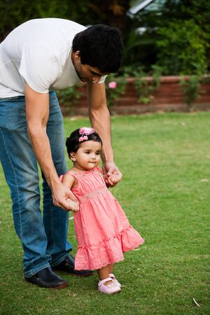 indian family: father helping his daughter to take first step of life Stock Photo