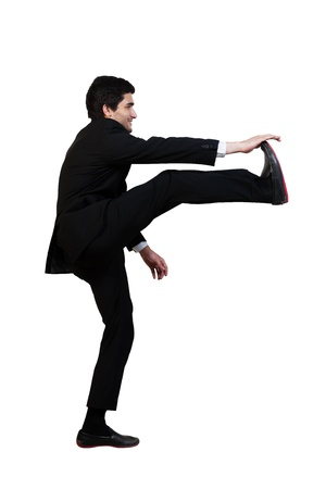 young businessman kicks in the air with aggression isolated on white photo