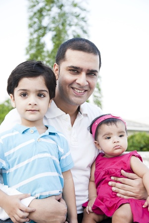 south asian: little baby girl and a little boy sitting in the lap of the father