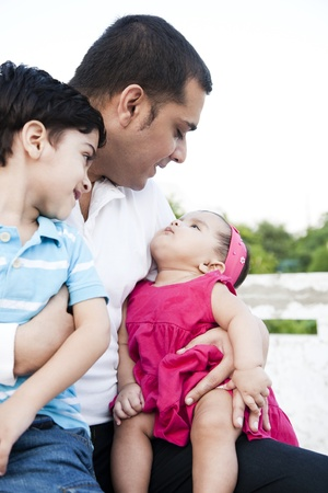 south asian ethnicity: little baby girl and a little boy sitting in the lap of the father