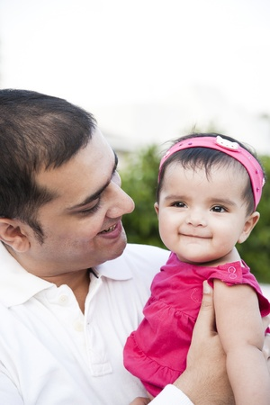 south asian: Portrait of a father holding the in his arms with love and affection