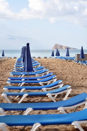 Empty beach only with its blue sunbeds Stock Photo
