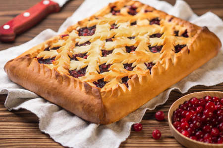 Pie with cranberries on a wooden table. Next to it lies a knife fresh and cranberries in a wooden plate. Decorated in a rustic style.