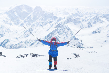 Elbrus, a mountaineer on the ascent, raised the trekking poles up 스톡 콘텐츠