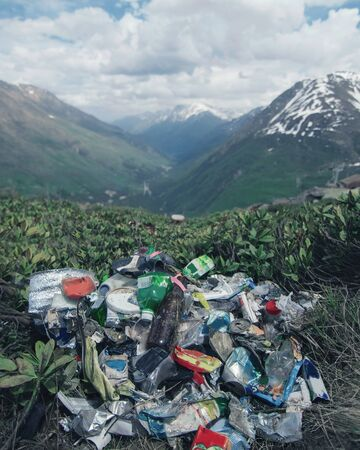 Garbage in the mountains, environmental pollution, environmental problem. Vertical format.