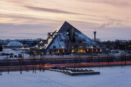 Kazan, Russia, January 28, 2020: cultural and entertainment complex pyramid in the winter against the sunset sky with lights on, tracers from cars. Editorial