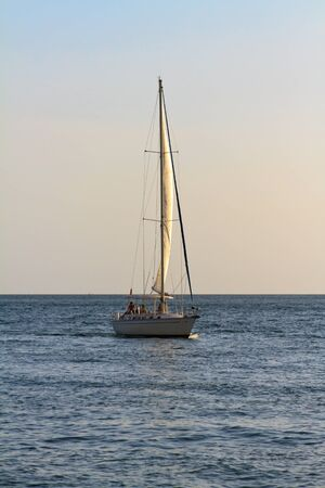 sailboat on sunset waters Stock Photo