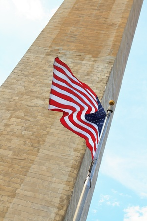 washington monument with american flag waving proudly